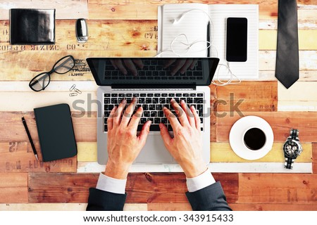 Typing businessman with laptop, cup of coffee, blank diary cover and glasses on wooden table, mock up - stock photo