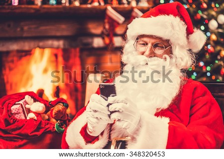 Typing message to elfs. Happy Santa Claus typing a message on the mobile phone and smiling while sitting at his chair with fireplace and Christmas Tree in the background - stock photo