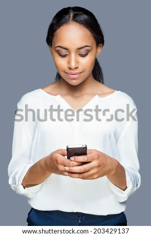 Typing message to friend. Confident young African woman holding mobile phone and looking at it with smile while standing against grey background - stock photo