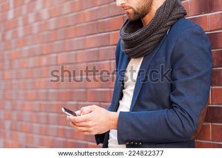 Typing message to friend. Side view of handsome young man in smart casual wear holding mobile phone while leaning at the brick wall - stock photo