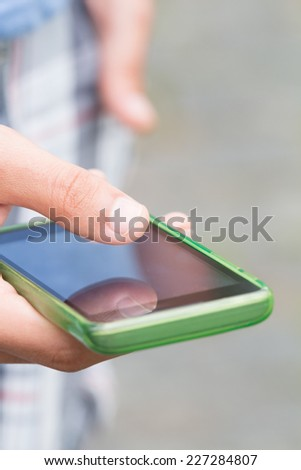 Typing messages on a smart-phone. Shallow depth of field.  - stock photo
