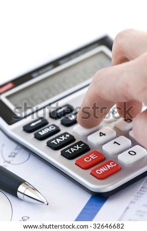 Typing  numbers for income tax return with pen and calculator - stock photo