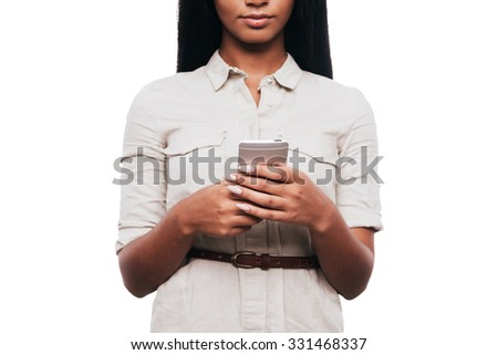 Typing quick message. Cropped image of confident young African woman holding mobile phone while standing against white background - stock photo