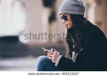 Typing quick message. Side view of beautiful young woman in sunglasses using her smartphone while sitting outdoors - stock photo