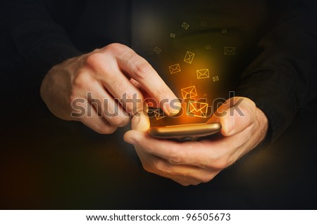 Typing text message on smartphone. Focus on hands and the phone device. Orange envelopes as incoming or outgoing messages. - stock photo