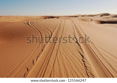 Tyre / Tire Tracks Through The Desert Sand Dunes - stock photo