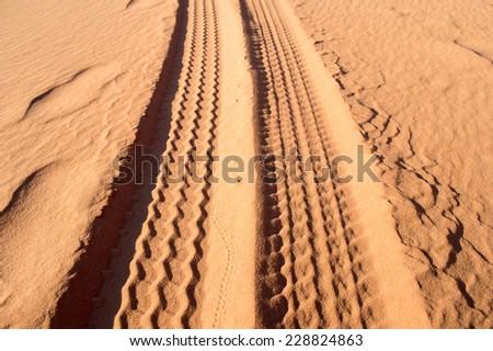 tyre tracks on the desert of wadi rum - stock photo