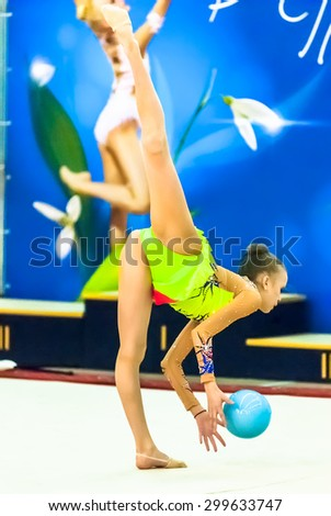 """Tyumen, Russia - April 4, 2015: All-Russian competitions in rhythmic gymnastics """"Spring grace"""". Sports complex """"Priboy"""". Young beautiful girl shows own skill in exercise with ball - stock photo"""