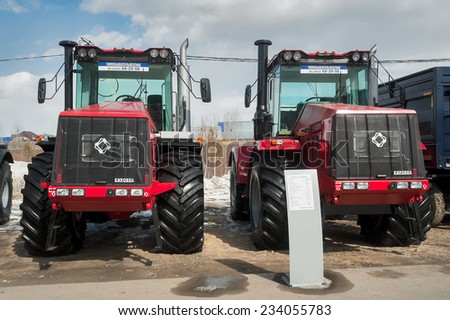 """Tyumen, Russia - April 04. 2014: IV Tyumen specialized exhibition """"Agricultural Machinery and Equipment"""". Tractors demonstration of Kirovskiy Factory production on platform open-air - stock photo"""