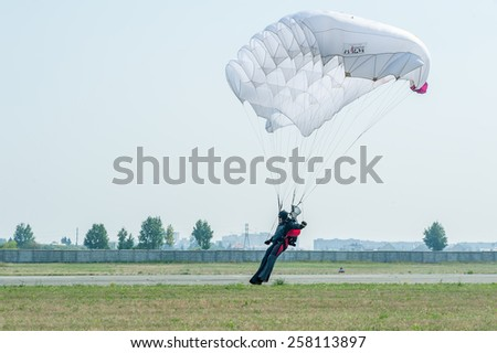 "Tyumen, Russia - August 11, 2012: Air show ""On a visit at UTair"" in heliport Plehanovo. Paratrooper men descend in show program - stock photo"