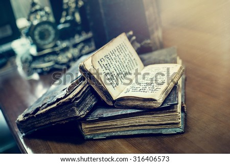 TYUMEN, RUSSIA - AUGUST 24, 2015: Antique hardcover books of 16th Century A.D. with Old Slavonic religious texts lying on a table in the Tyumen State University Library and Learning Center.  - stock photo