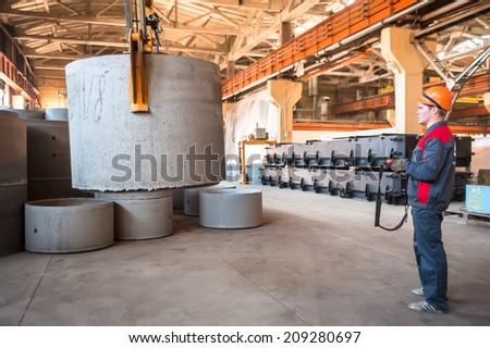 Tyumen, Russia - August 13, 2013: Circle pit making department at construction material factory ZHBI-5 (Concrete Goods Plant No. 5). Worker moving prepared unit to warehouse - stock photo