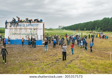 Tyumen, Russia - August 8, 2015: Steel Character command extrim race project on Krugloe lake and Gagarin park.  Vertical world stage - high wooden fence with ropes. Teams storm wall - stock photo