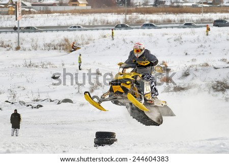 Tyumen, Russia - December 26. 2009: Sport snowmobile racing on championship of Ural region. Snowmobile jump - stock photo