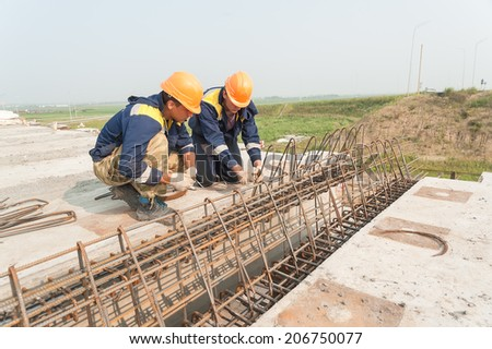 Tyumen, Russia - July 31, 2013: JSC Mostostroy-11. Bridge construction for outcome of the Tobolsk path and Bypass road round Tyumen. Two workers do fittings binding - stock photo