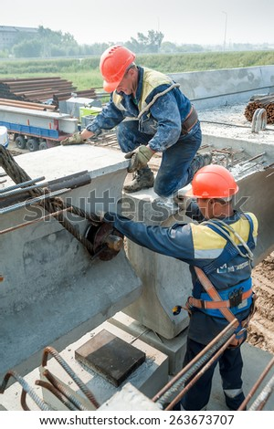 Tyumen, Russia - July 31, 2013: JSC Mostostroy-11. Bridge construction for outcome of the Tobolsk path and Bypass road round Tyumen. Two workers busy on bridge construction - stock photo