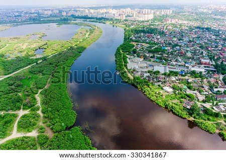 Tyumen, Russia - June 3, 2015: Aerial view onto disrict of private houses on bank of Tura river. Zarechnye residential districts on background - stock photo