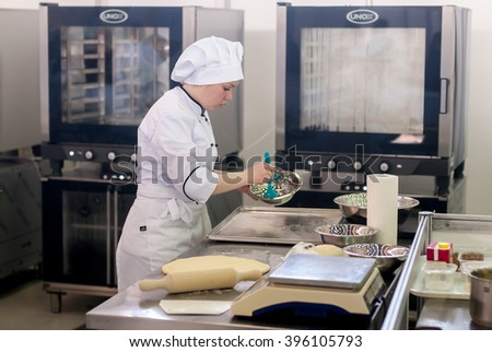 Tyumen, Russia - March 23. 2016: Open championship of professional skill among youth. World skills Russia Tyumen - 2016. Girl-cook prepares food in competition of masters of cook business - stock photo