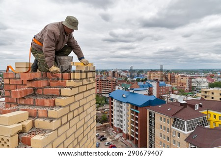 Tyumen, Russia - May 23, 2008: Bricklayer works on construction of 18 floor brick residental house at intersection of streets of Gercena and Chelyuskincev. Bricklayer behind work - stock photo