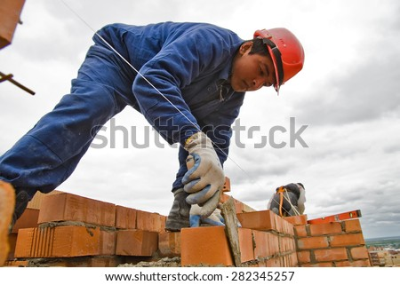 Tyumen, Russia - May 23, 2008: Construction of 18 floor brick residental house at intersection of streets of Gercena and Chelyuskincev. Bricklayer behind work. It is demolished because of bad base - stock photo