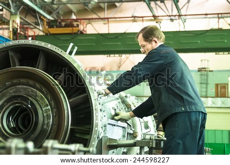 Tyumen, Russia - November 14, 2007: JSC Tyumenskie Motorostroiteli. Plant on production and repair of aviation engines. Elderly mechanic assembles aviation engine - stock photo