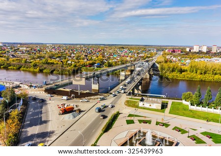 Tyumen, Russia - September 17, 2015: Aerial view of Tura river and bridge on Chelyuskinskaya street. Nearby there is construction of new one.  - stock photo