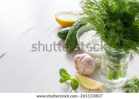 Tzatziki sauce ingredients - yogurt, cucumber, lemon, mint, dill on white wood background, closeup - stock photo