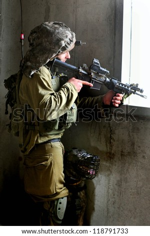TZEELIM - MARCH 31:Israeli soldier looks through a gun-sight during Urban Warfare Exercise on March 31 2011 in Tzeelim, Israel. The terrain and civilians makes it very difficult to identify the enemy - stock photo