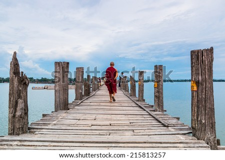 U Bein Bridge, Myanmar-Aug 26th, 2014: Myanmar monks walk on U Bein Bridge where is the oldest and longest teak wooden bridge in the world. - stock photo