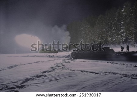 U.S. Army 3-inch mobile gun firing on enemy positions at night in northwest France. In Dec. 1944 Allied armies were clearing Germans out of Saarlautern and Alsace-Lorraine. B&W Photo with oil color. - stock photo