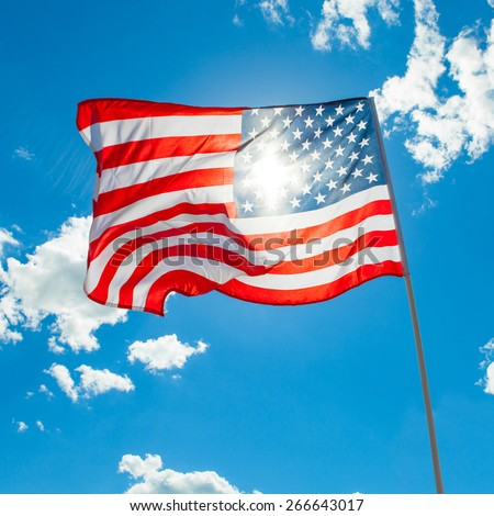 U.S. flag and cumulus clouds on background - stock photo