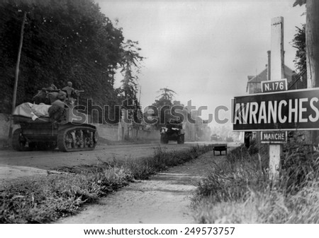 U.S. light tanks passing a road sign for the town of Avranches, southeast of the Falaise Pocket. First U.S. Army's battle against Germans' Operation Luttich in Normandy. August 1-2, 1944. - stock photo