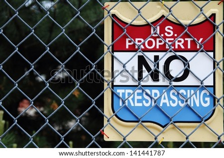 U.S. Property No Trespassing sign attached to a chain link fence. - stock photo