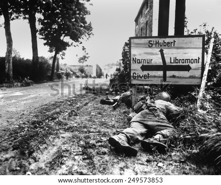 U.S. Soldiers pinned down by German small arms fire in the Belgian town of Libin. Sept. 7, 1944. - stock photo