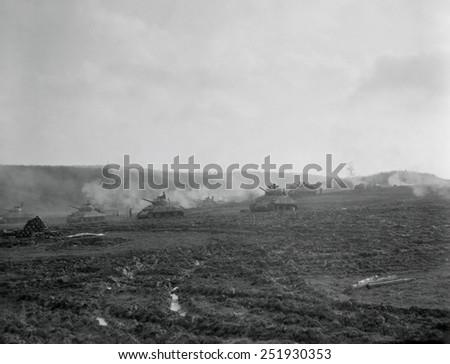 U.S. tanks assembled outside of a German town open fire at the beginning of an assault. Nov. 16, 1944. World War 2. - stock photo