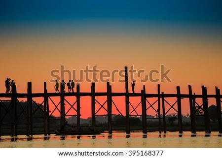 Ubein teak wood bridge and people against sunlight in sunset tim - stock photo