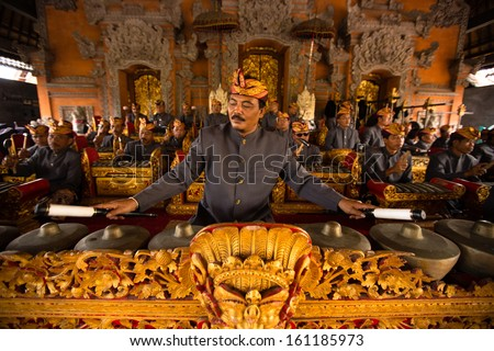 UBUD, BALI, INDONESIA - NOV 1: A man plays traditional gamelan percussion during the ceremony of the cremation of the Queen on November 1, 2013 in Ubud, Bali. - stock photo