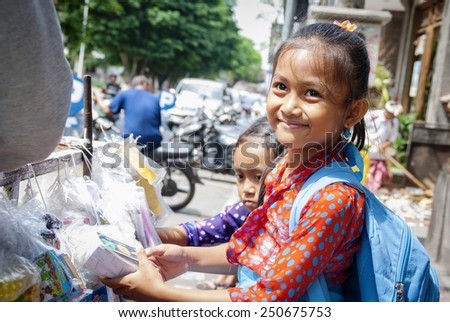 UBUD, INDONESIA - SEPTEMBER 23: Two adorable and smiling schollgirls buying goods at the street in Ubud, Bali Indonesia on September 23, 2014 - stock photo