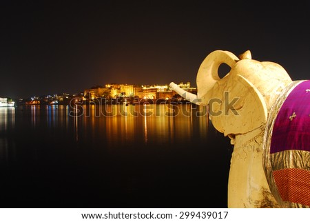 Udaipur India by night, stone elephant, view of palace and lake/ Udaipur India at night - stock photo