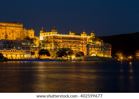 UDAIPUR, INDIA - 20TH MARCH 2016: A view towards the City Palace from Pichola Lake in Udaipur at night. Lights can be seen on the building. - stock photo