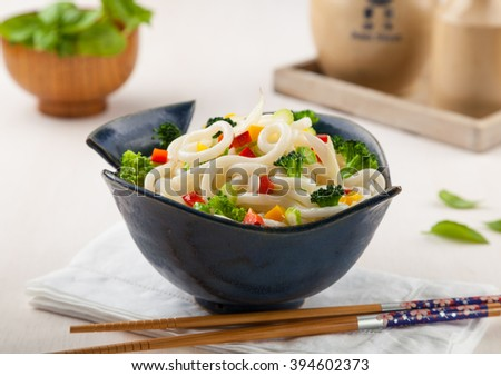 Udon, Japanese noodles with vegetables in a handmade ceramic bowl. - stock photo