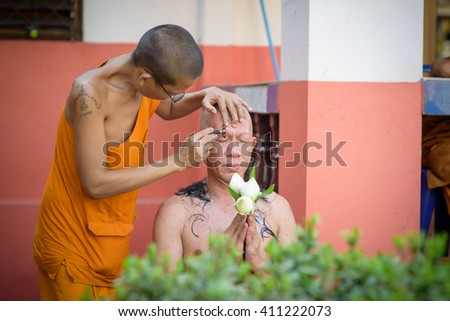 UDONTHANI, THAILAND - APIRL 6 2016 : Priest is cutting the hair of the naga or new priest preparing for the Buddhist Monks ordination in Udonthani, Thailand - stock photo