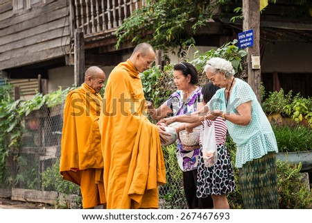 UDONTHANI, THAILAND - APRIL 6 2015 : Unidentified monks receive food offering from people on April  6, 2015 in Udonthani, Thailand. Offering food is one of most common rituals in Buddhism. - stock photo