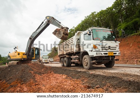 Udonthani - Thailand, Aug 8, 2014; dump truck unloading soil on the sand at a construction site. - stock photo
