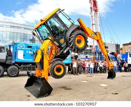 "UFA, RUSSIA - MAY 23: Demonstration of of the JCB 3CX tractor abilities at the annual International exhibition ""Gas. Oil. Technologies"" on May 23, 2012 in Ufa, Bashkortostan, Russia. - stock photo"