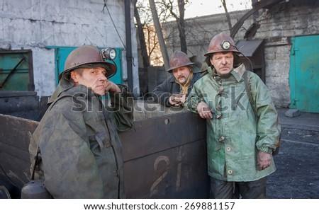 Uglegorsk, Ukraine - March, 12, 2014: Miners look on near empty mining trolley at mine Uglegorskaya on March 12, 2014 in Uglegorsk, Ukraine - stock photo