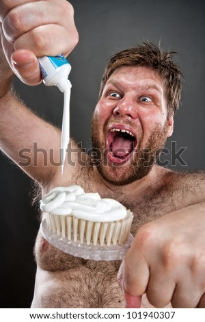 Ugly man preparing to brushing teeth - stock photo