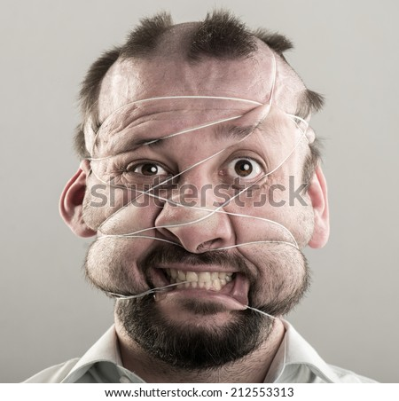 Ugly man tied with strings on his face - stock photo