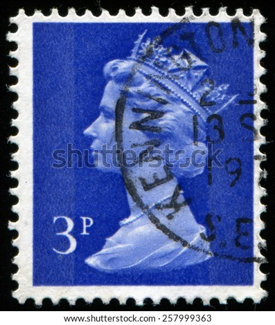 UK-CIRCA 1971:postage stamp printed in United Kingdom shows image of Elizabeth II is the constitutional monarch of 16 sovereign states known as the Commonwealth realms, in blue background, circa 1971. - stock photo