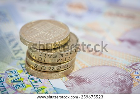 UK Money Stack of Pound Coins on Notes - stock photo